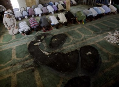 Palestinians pray inside a partially burned mosque in the West Bank village of Beit Fajjar