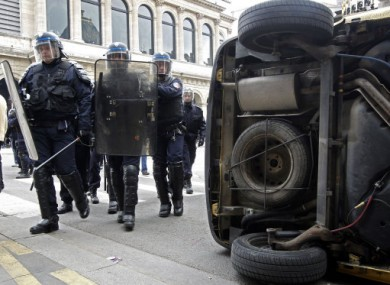 Riot police officers walks by an overturned car during a students demonstration in Lyon today.