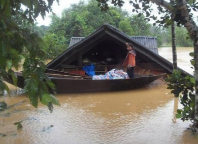A girl stands on a boat in front of her flooded home in central Ha Tinh province, Vietnam