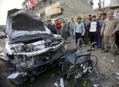 People inspect a destroyed car and a wheelchair at the scene of a car bomb attack Baghdad, Iraq, today.