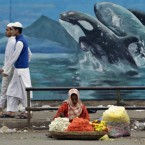 An Indian street flower vendor sets up for the day on a pavement in Bangalore in front of a dolphin mural which is part of city's beautification drive.