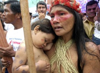 A indigenous Huaorani woman holds her son during a protest outside against Chevron-Texaco in 2003.