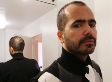 With the back of his head reflected in a mirror, artist Wafaa Bilal poses for a photograph.