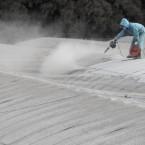 A farmer blows volcanic ash from Shinmoedake off a vinyl house in the Kirishima mountains range on 29 January, 2011. (Motoki Nakashima/AP/Press Association Images)