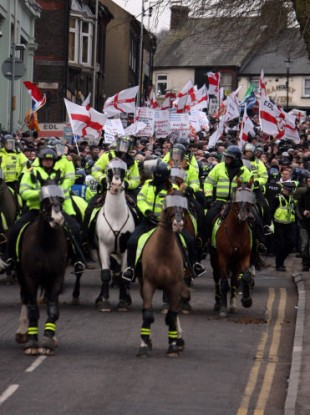 A group of English Defence League members are watched by mounted police as they march through Luton today.