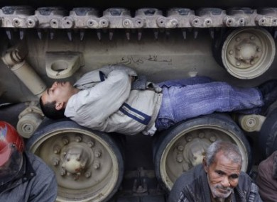 Protester sleep under - and on - tanks to prevent them moving as they occupy Tahrir Square, Cairo.