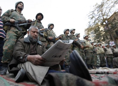 A protester reads a newspaper as he sits before a line of Egyptian Army soldiers in Tahrir Square, Cairo, today.