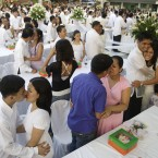 Newly-wed Filipino couples kiss during ceremonies at a mass wedding in the suburban city of Taguig, south of Manila. About 140 couples joined the mass wedding sponsored by local government officials. (AP Photo/Aaron Favila)