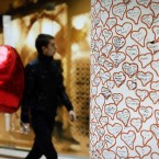 A Bulgarian carries red heart balloon for Valentine's day as he passes by a column decorated with hearts in Sofia. (AP Photo/Valentina Petrova)