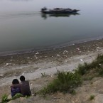 An Indian couple share a moment as a boat passes by on the river Brahamaputra, Gauhati, India. (AP Photo/Altaf Qadri)