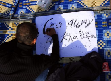 A Bahraini anti-government protester prepares a sign at a makeshift camp at the Pearl roundabout in Manama, Bahrain, today.