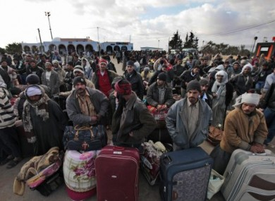 Egyptians, who used to work in Libya, wait for buses to take them further inland today after fleeing Libya.