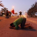 A Bahraini protester prays in the street in front of tanks in Manama, Bahrain during this week's uprising against the government. (AP Photo/Hasan Jamali)