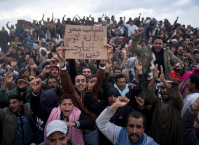Crowds of Egyptian workers who crossed the Tunisian border out of Libya react to a photographer today.