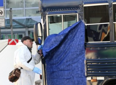 A police officer inspects the shattered windscreen of a bus outside Frankfurt Airport after a gunman opened fire on US soldiers on board today.