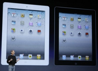 Apple CEO Steve Jobs stands under images of the iPad 2 at an Apple event in San Francisco this evening.