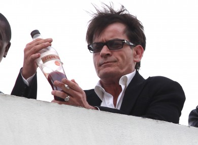 Charlie Sheen drinks from a bottle labelled 'tiger blood' in LA last week. The actor is to kick off a live tour, though the contents of the show are unknown.