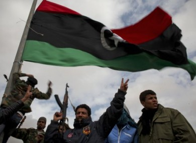 Libyan volunteers gesture as they raise a pre Gadhafi flag on the outskirts of the eastern town of Ras Lanouf, Libya, yesterday.