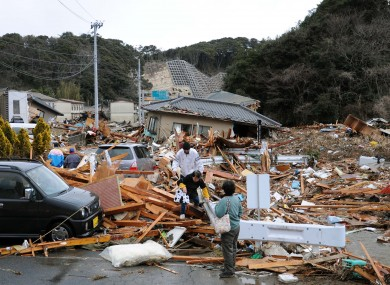 Residents walk through the rubble of houses collapsed by the earthquake in Iwaki, Fukushima state