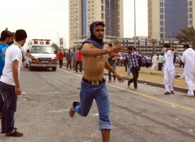 An anti-government protester clears the way for an ambulance during demonstrations in Manama yesterday.