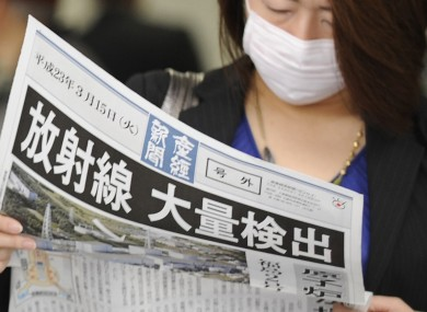 A masked woman wears a newspaper with a banner headline: