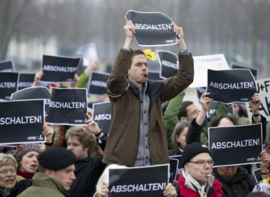 Anti-nuclear demonstrators in Berlin today bear signs saying