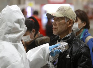 An evacuee is screened for radiation exposure in the Fukushima prefecture, Japan, yesterday.