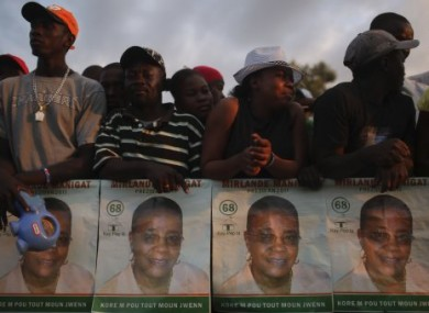 People gather with images of Haitian presidential candidate Mirlande Manigat at a campaign rally on Friday.