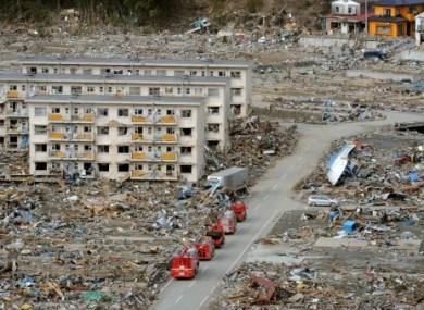 Fire trucks go through a residential area of the Miyagi Prefecture, where police say over 15,000 people may have died.