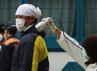 A man is screened for radiation exposure from Fukushima at an evacuation centre yesterday.