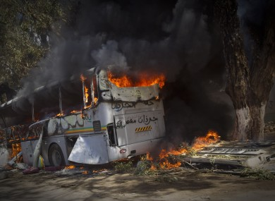 A bus burns on the side of a road outside Benghazi today.