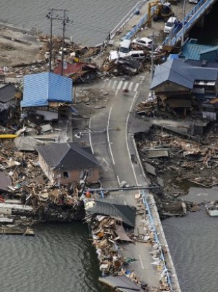 Debris from tsunami-stricken houses being removed from a bridge in Ishinomaki, Miyagi Prefecture, Japan, Tuesday, March 22.