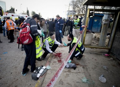 Israel rescue workers and paramedics clean a pool of blood at a bus stop in Jerusalem following this lunchtime's explosion.