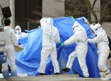 A man who had been working to restore power and cooling functions at the Fukushima Daiichi nuclear plant walks to a special vehicle for radioactive decontamination, while being shielded with a blue sheet to conceal his identity