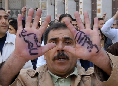 Anti-Syrian government protester, displays Arabic words on his hands, reading