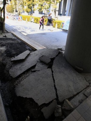 People walk past a damaged road outside of Tokyo Disneyland in Urayasu, east of Tokyo, Japan, Tuesday, March 29, 2011. Tokyo Disneyland was shut down after the March 11 earthquake and has been closed ever since.