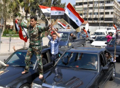 A Syrian soldier waves Syrian flags during a pro-Assad demonstration in Damascus yesterday.