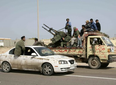 Libyan rebels in a car and a truck with a mounted weapons system leave Ras Lanouf, Libya on Wednesday