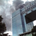 Black smoke rises from a burning building in Tokyo's Odaiba area after Japan was struck by a magnitude 8.9 earthquake. (AP Photo/Kyodo News)