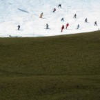 Skiers crowd a slope next to a green meadow in the Lofer skiing resort in the Austrian province of Salzburg. (AP Photo/ Kerstin Joensson)