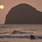 A dog splashes in the surf as the sun sets in front of Gull Rock off the coast of Cornwall. Pic: Ben Birchall/PA Images.