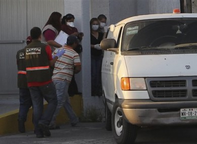 Forensic workers prepare to transfer bodies from a van into a large truck, not seen, in the northern border city of Matamoros, Mexico on Wednesday