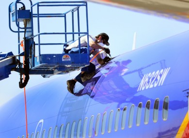 A worker investigating the emergency landing of Southwest Airlines flight 812 cuts away a portion of the plane's fuselage in Arizona yesterday.