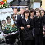 PSNI Constable Ronan Kerr's mother Nuala and family follow Ronan's coffin through their home town of Beragh in Co Tyrone, to the Church of the Immaculate Conception where his funeral is taking place.