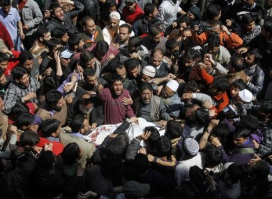 Kashmiri Muslims shout slogans as they crowd around the body of Moulvi Showkat Ahmed Shah