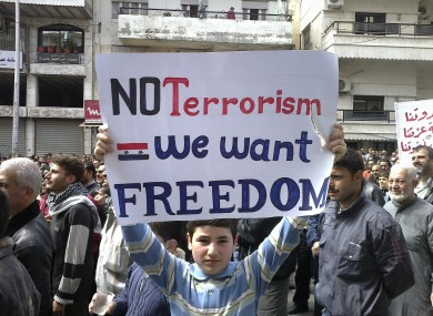 A Syrian boy carries a banner during an anti-government demonstration in the coastal city of Banias, Syria on Friday.