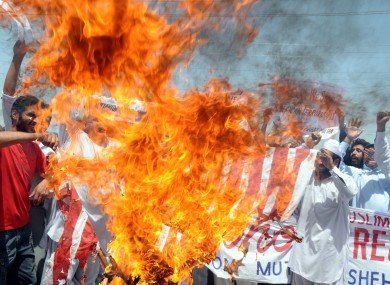 Pakistani protesters burn a representation of the US flag during a rally to condemn US drone attacks in Pakistani territory on Friday.