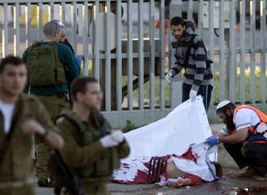 Israeli security officers and paramedics examine the body of the Jewish worshipper shot and killed in Nablus on Sunday