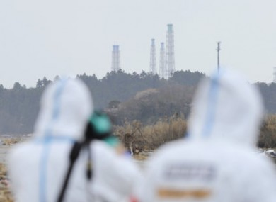 The exhaust stacks of the Fukushima Daiichi plant tower above woodland.