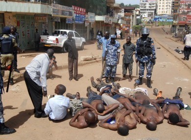 Ugandan rioters are made to lay down on the road after their arrest by Ugandan police on Friday